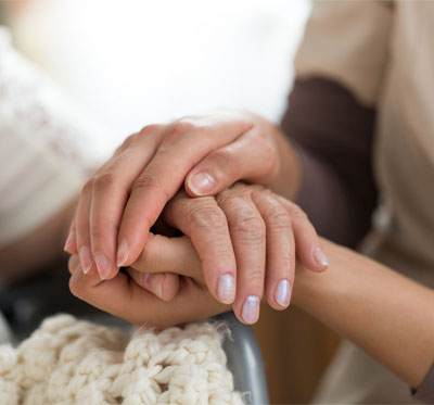 A young woman holds an older woman's hands